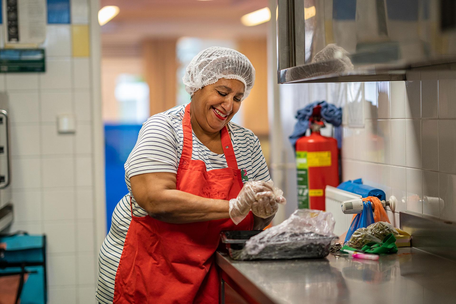 Vrouw lachend aan het koken