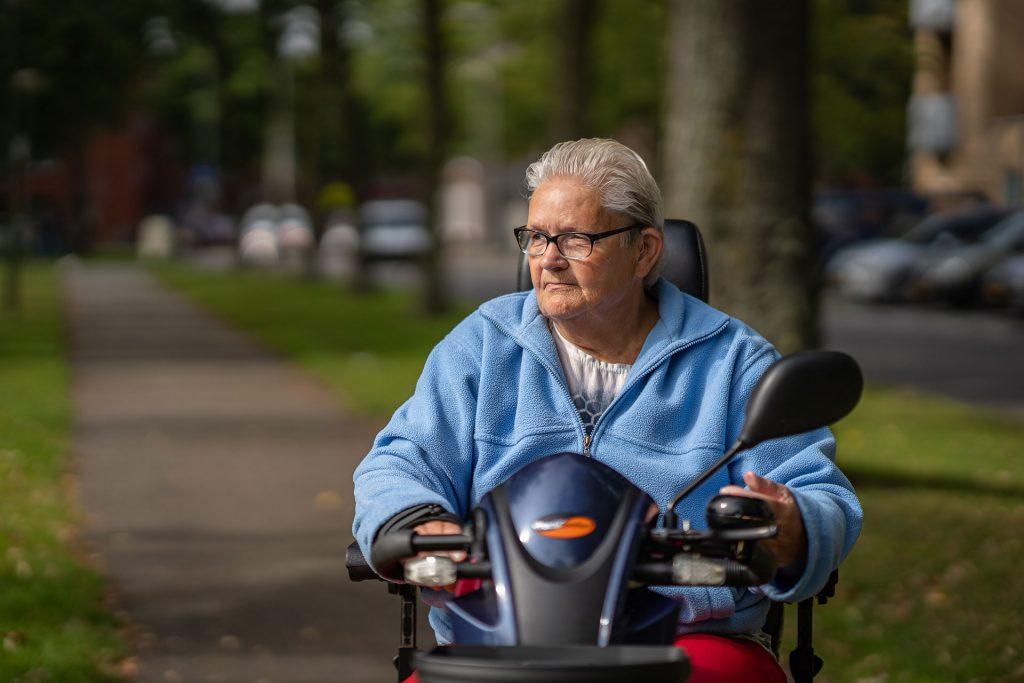 Oudere vrouw op scootmobiel